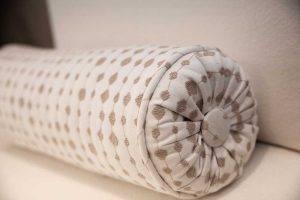 detail of white and tan neck roll pillow